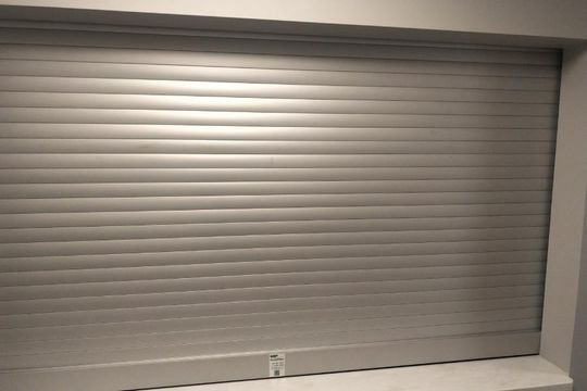 view of a garage with closed roll shutter